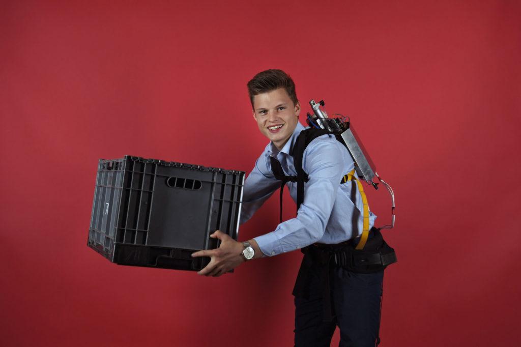 Junger Mann im blauen Hemd vor roter Wand, der eine scheinbar schwere, schwarze Kiste mit ausgestreckten Armen heben kann, weil er auf dem Rücken eine metallische Box trägt, die ihm irgendwie dabei hilft. (Foto: Jugend forscht)