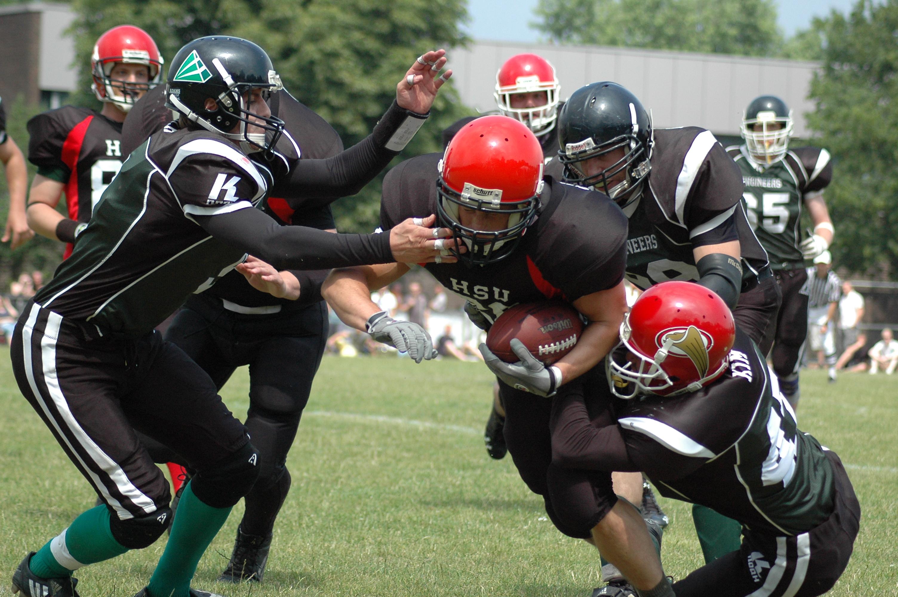Mehrere sehr stark gepolsterte Männer mit roten oder schwarzen Helmen kämpen auf grünem Rasen um einen rotbraunen Kunstlederball in der Form eines verlängerten Rotationsellipsoids mit spitzen Enden. (Foto: Dietmar Strey)