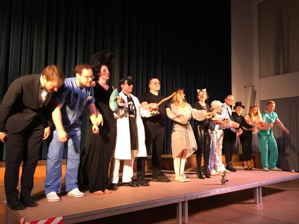 Auf einer Bühne steht eine Reihe kostümierter Menschen, die sich an den Händen halten und verbeugen.