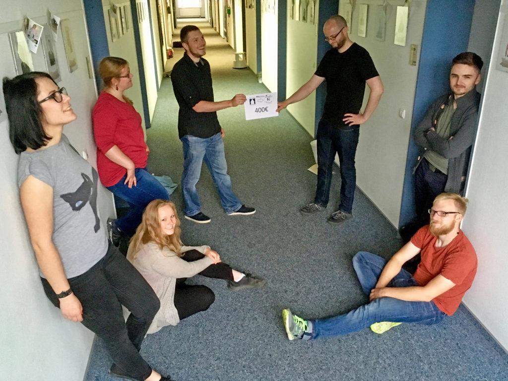 Sieben junge Menschen in verschiedenen Posen auf einem langen Flur, zwei von Ihnen halten ein Schild mit der Aufschrift 400 Euro.