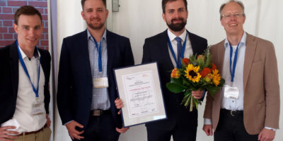 Vier teils bärtige Herren, von denen einer eine Urkunde und einen Blumenstrauss trägt; er ist Preisträger des Young Professionals' Award Logistics.