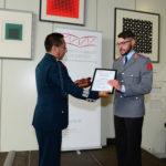 Ein älterer Mann in einer prächtigen Uniform überreicht eine Urkunde und eine Plakette an einen jüngeren Mann in einer etwas schlichteren Uniform.