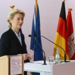Eine blonde Dame im blauen Kostüm an einem Rednerpunlt, dahinter bunte Fahnen.