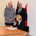 Eine blonde Dame in einem blauen Kostüm unterschreibt ein Dokument, hinter ihr stehen ein Soldat in einer Generalsuniform und ein Mann in einem dunklen Anzug.