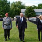 Ein Soldat in Uniform, ein Mann in einem dunklen anzug und eine Frau in einem blauen Kostüm gehen vor einer Reihe angetretener Soldaten längs.
