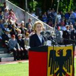 Eine blonde Dame im blauen Kostüm steht hinter einem Rednerpult, das in eine Bundesdienstflagge eingehült ist, dahinter sitzen Männer in bunten Uniformen auf einer Tribüne.