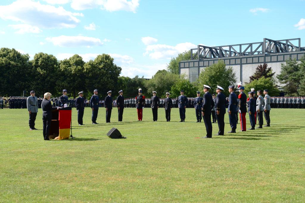 Eine blonde Dame im bvlauen Kostüm spricht hinter einem Rednerpult zu Soldatinnen und Soldaten, die um sie herum angetreten sind und in Grundstellung stehen.