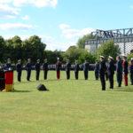 Eine blonde Dame im blauen Kostüm spricht hinter einem Rednerpult zu Soldatinnen und Soldaten, die um sie herum angetreten sind und in Grundstellung stehen.