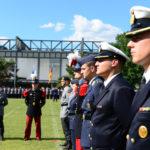 Soldaten in bunten Uniformen stehen im Karree vor einer angetretenen Paradeaufstellung.
