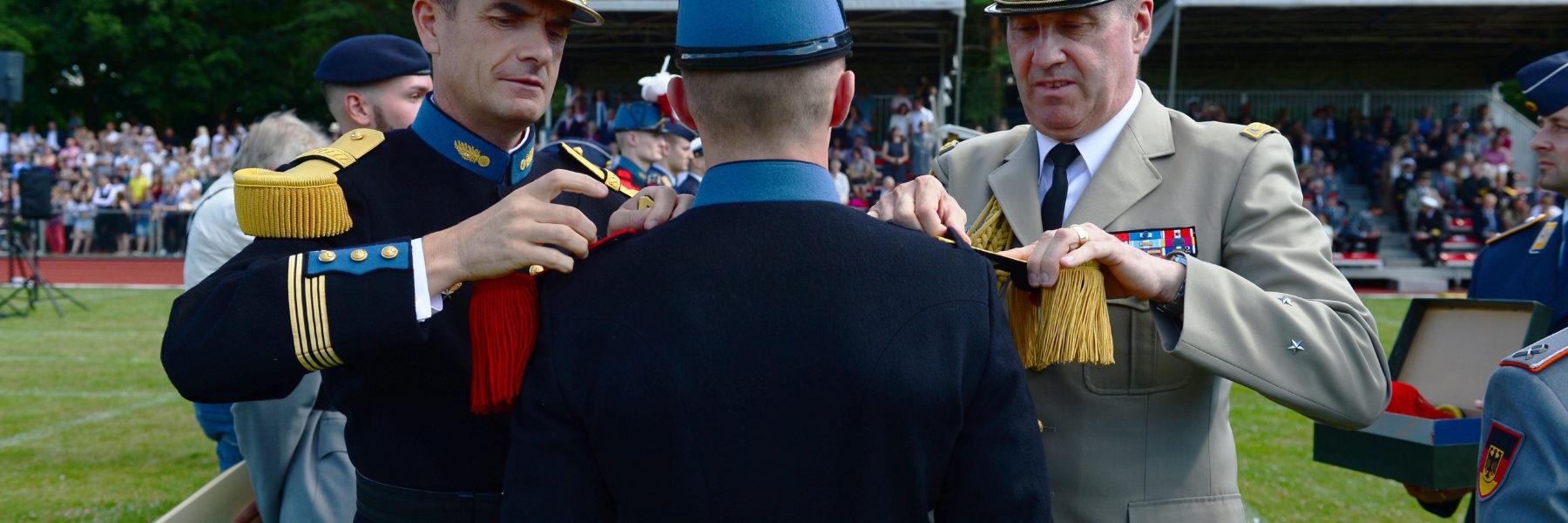 Zwei Soldaten in bunten Uniformen stecken einem dritten Soldaten mit Federbusch am Hut neue Epauletten auf die Schulter.