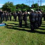 Männer und Frauen in Marineuniformen mit Blasinstrumenten, einer dirigiert.