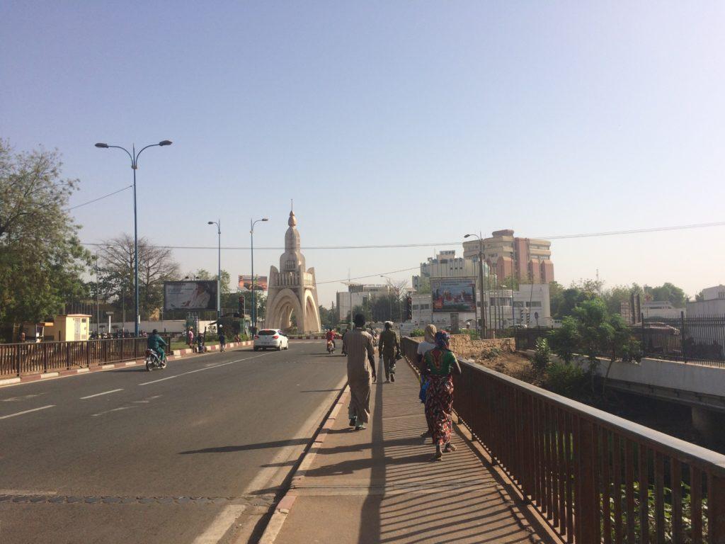 Menschen mit dunkler Haut in exotischen Gewändern gehen über eine Brücke, im Hintergrund Gebäude