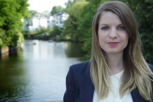 Junge Frau mit schulterlangen Haaren steht auf einer Brücke über einem Fluss, im Hintergrund unscharf weiße Häuser und grüne Bäume