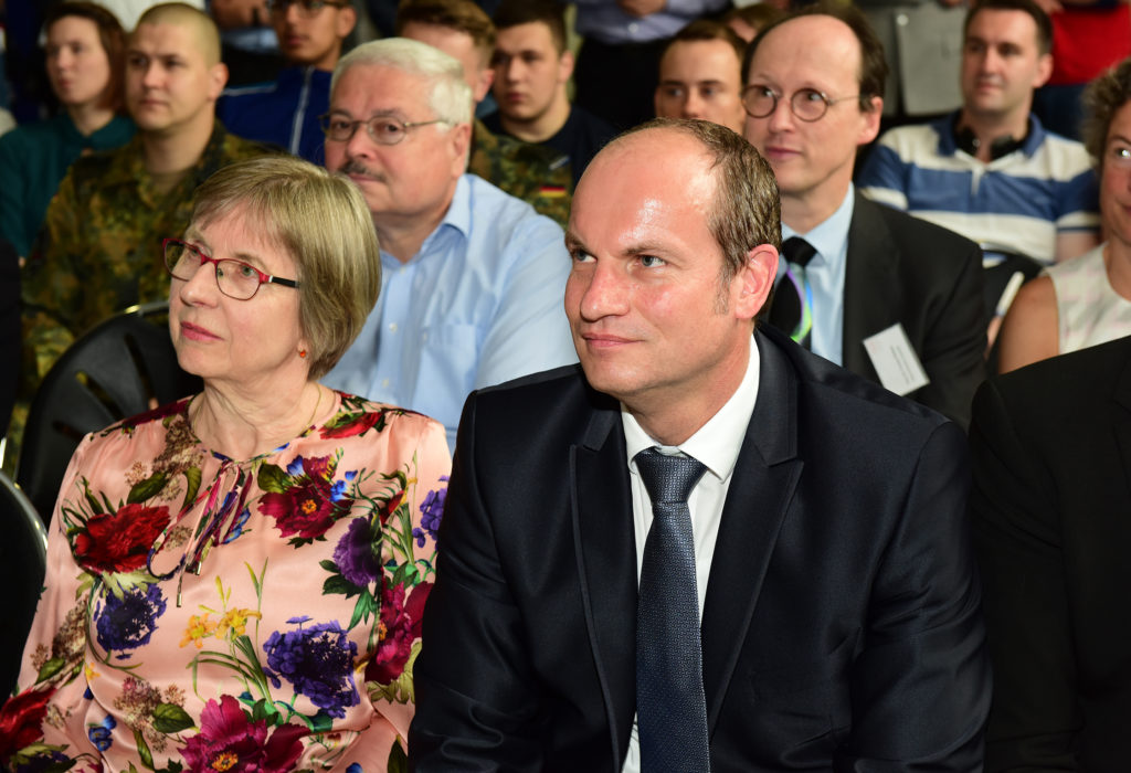 Eine Dame in einem geblümten Kleid und ein Herr in einem dunklen Anzug schauen interessiert nach oben links.