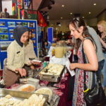 Eine junge Frau schaut auf das in Warmhaltebehältern ausgelegte Essen, dahinter stehen zwei uniformierte junge Frauen mit Kopftüchern.