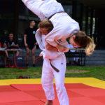 Eine junge Frau in einem Judo-Anzug wirft eine andere junge Frau im Judo-Anzug über ihren Kopf.