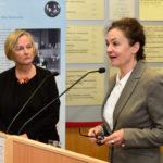 Eine blonde Frau schaut auf eine dunkelhaarige Frau, die hinter einem Rednerpult steht.