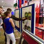 Drei junge Menschen stehen vor einem Plakat mit bunten Bildern.