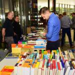 Ein junger Mann im blauen Hemd schaut auf einen großen Bücherstapel.