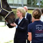 """Eine blonde Dame im blauen Kostüm streichelt ein Pferd, davor steht eine junge Frau in einem blauen Polohemd mit der Aufschrift """"Studentenreiter der Bundeswehr"""""""