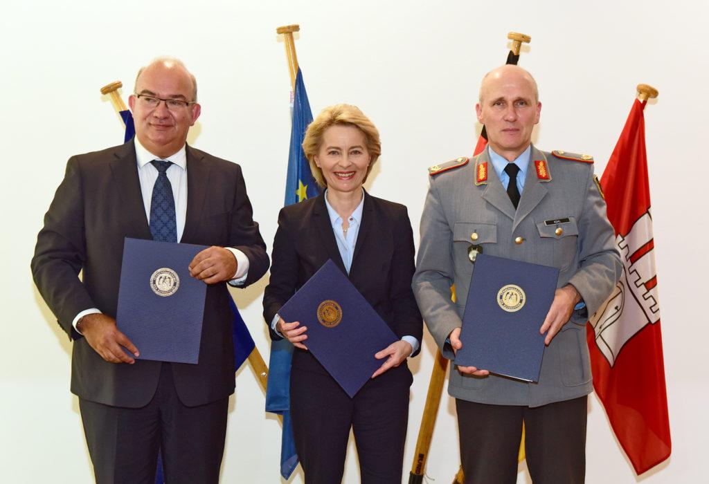 Ein Mann in einem Dunklen Anzug, eine Frau im dunklen Kostüm und ein Soldat in Generalsuniform halten Blaue Dokumentenmappen mit einem goldfarbenen Prägewappen.