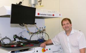 Ein Mann im weißen hemd sitzt vor einem technischen Gerät.