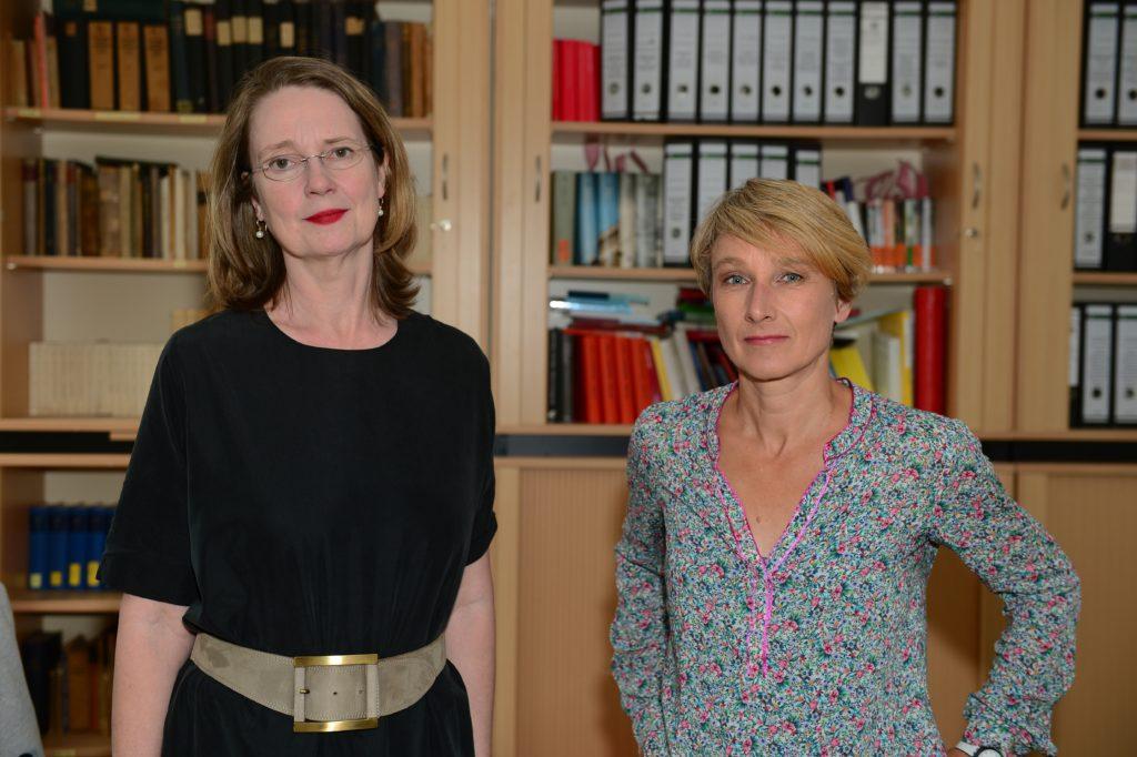 Zwei Damen vor Bücherregalen.