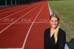 Eine junge Frau mit langen blonden Haaren steht auf einem Sportplatz.