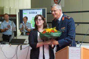 Ein Mann in der Uniform eines Luftwaffengenerals überreicht einer Frau einen bunten Blumenstrauß.