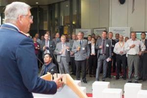 EIn Mann in der Uniform eines Luftwaffengenerals spricht hinter einem Rednerpult zu einer großen Gruppe von Menschen