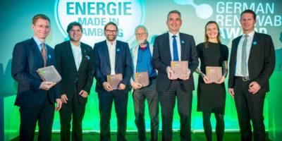 7 Menschen stehen auf einer Bühne, darunter 6 Männer und nur eine Frau. Die Frau ist die Hauptperson. Sie hält eine Tafel, auf der German Renewables Award 2018 steht.