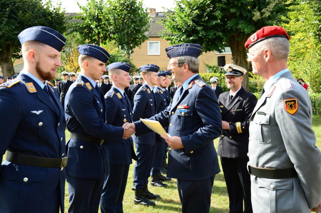 Ein Soldat in einer Generalsuniform der Luftwaffe überreicht eine Urkunde an einen jüngeren Soldaten.