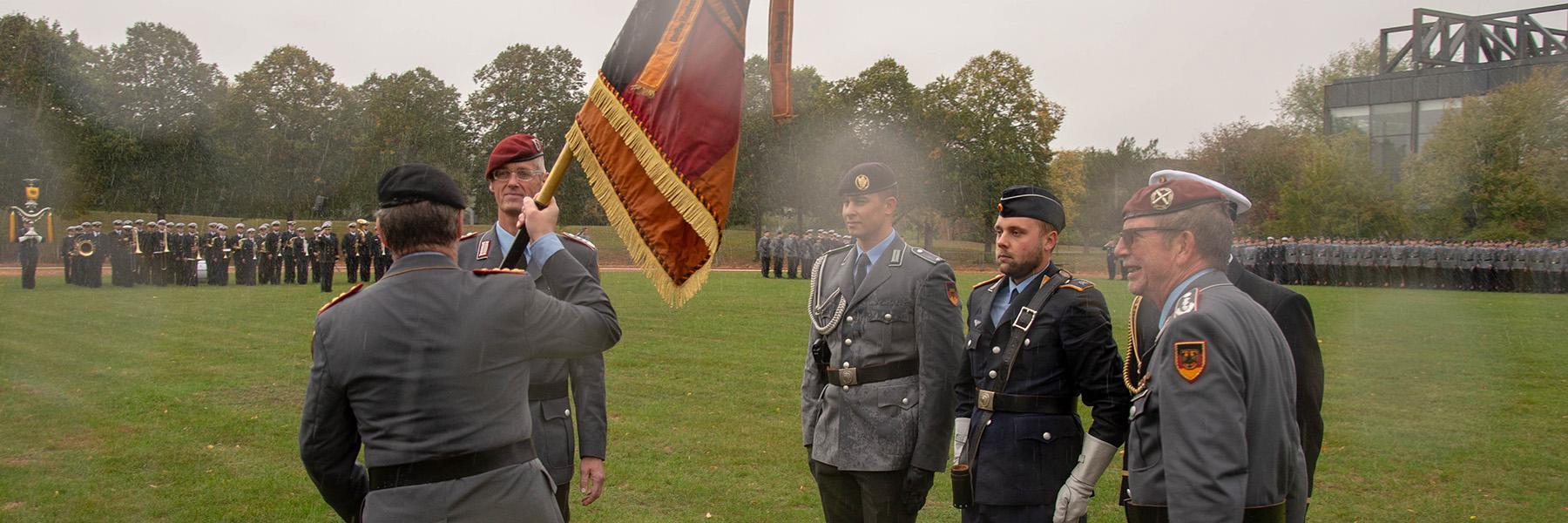 Männer in nassen Uniformen stehen auf dem Rasen, im Hintergrund steht eine Formation aus ebenfalls nassen Soldatinnen und Soldaten; einer übergibt eine Flagge an einen anderen.