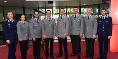 Eine Reihe augenscheinlich glücklicher Menschen in Uniform, auf einem roten Teppich stehend.