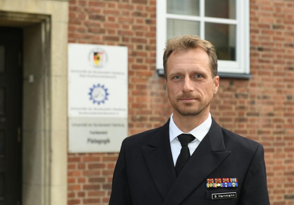 Ein dunkelblonder Mann mit Bart in einer marineuniform.