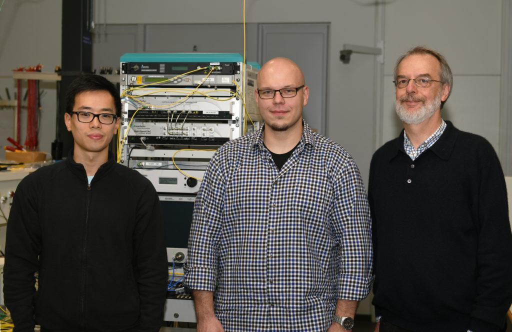 Drei Männer in einem Laboratorium mit technischen Geräten.