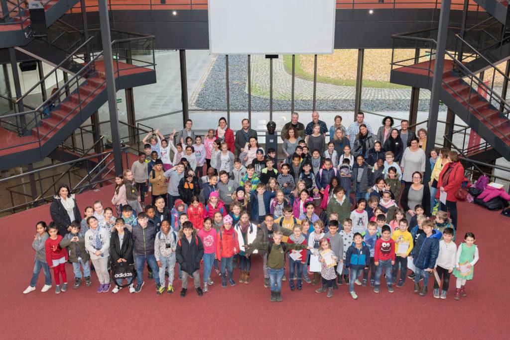 Viele Kinder und ein paar Erwachsene stehen auf einem roten Teppich.