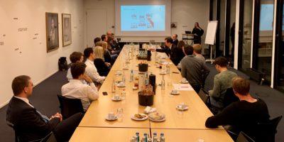 Menschen sitzen um einen Konferenztisch und schauen auf eine grünliche schimmernde Projektionswand.