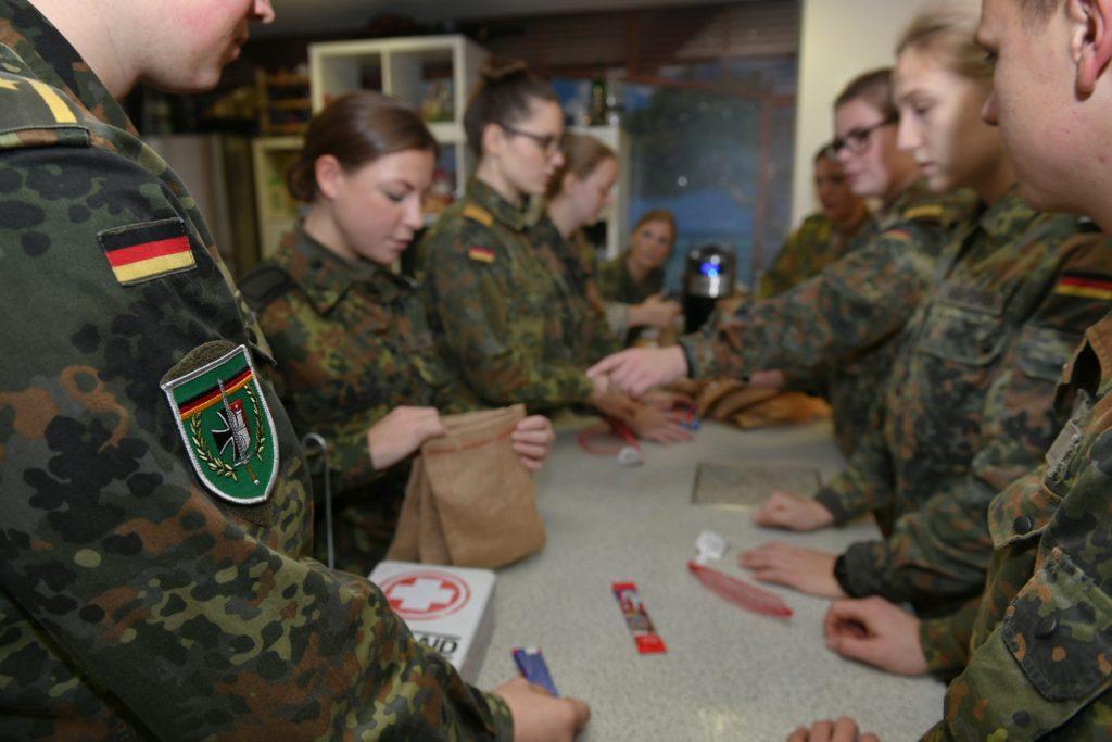 Soldatinnen und Soldaten im Flecktarnanzug hantieren in einer Küche mit Süßigkeiten und Jutebeuteln.