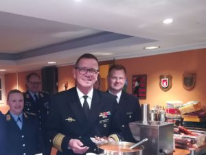 Menschen in Uniform, in der Mitte ein Admiral mit einer Bratwurst in roter Soße.