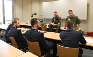 Soldaten in Uniform sprechen mit anderen Soldaten, die eine Fliegerkombi tragen.