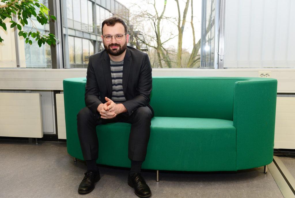 Ein Mann mit Vollbart auf einem türkisfarbenen Sofa