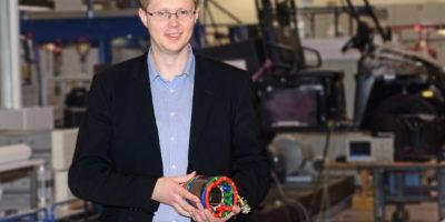 Ein mann, der ein Teil eines Elektromotors in der Hand hält