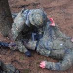 Ein Soldat im Kampfanzug bindet einem anderen Soldaten mit einer Aderpresse den Oberschenkel ab.