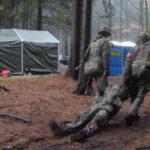 Zwei Soldaten schleifen einen dritten durch den Wald.