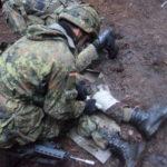 Zwei Soldaten im Kampfanzug bemühen sich um einen vermeintlich verletzten Dritten