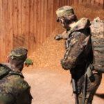 Zwei Soldaten schauen auf einen Sandhaufen.