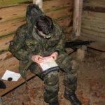 Ein Soldat mit einer Grubenlampe am Kopf schaut auf eine gefaltete Landkarte auf seinen Knien.