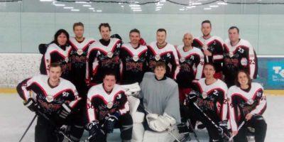 Menschen in Eishockey-Montur knien und stehen auf einer Hallen-Eisfläche. Keiner trägt einen Helm, aber einige haben ihre Eishockeyschläger gekreuzt.