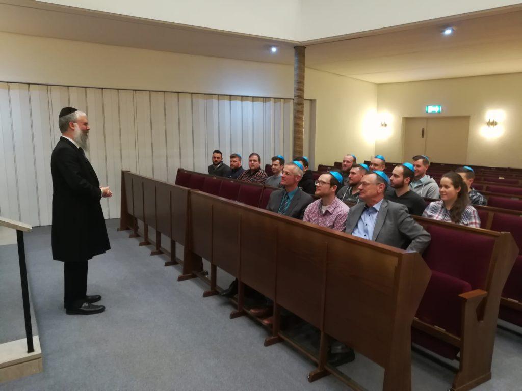 Ein Rabbiner spricht zu einer Gruppe von Menschen, von denen die männlichen alle eine blaue Kipa tragen